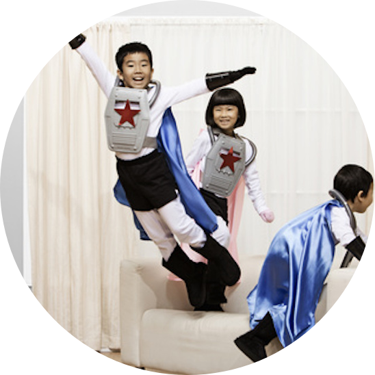 Three kids wear superhero costumes